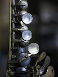 "In this Dec. 8, 2012 photo, a saxophone repaired with coins and keys by Tito Romero sits in Romero's workshop at his home in Capiata, Paraguay. Romero was repairing damaged trumpets in a shop outside Asuncion until Favio Chavez, the creator of ""The Orchestra of Instruments Recycled From Cateura,"" asked him to turn galvanized pipe and other pieces of metal into flutes, clarinets and saxophones for his students. (AP Photo/Jorge Saenz)"