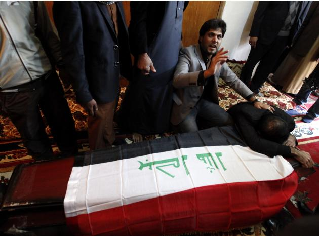 Mourners react next to the coffin of Joumaili during his funeral in Falluja