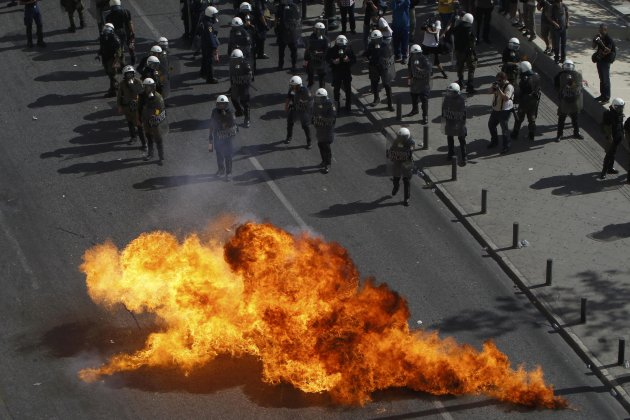 Flames from a molotov cocktail flare up near Greek riot police as they stand guard near an anti-austerity march in central Athens