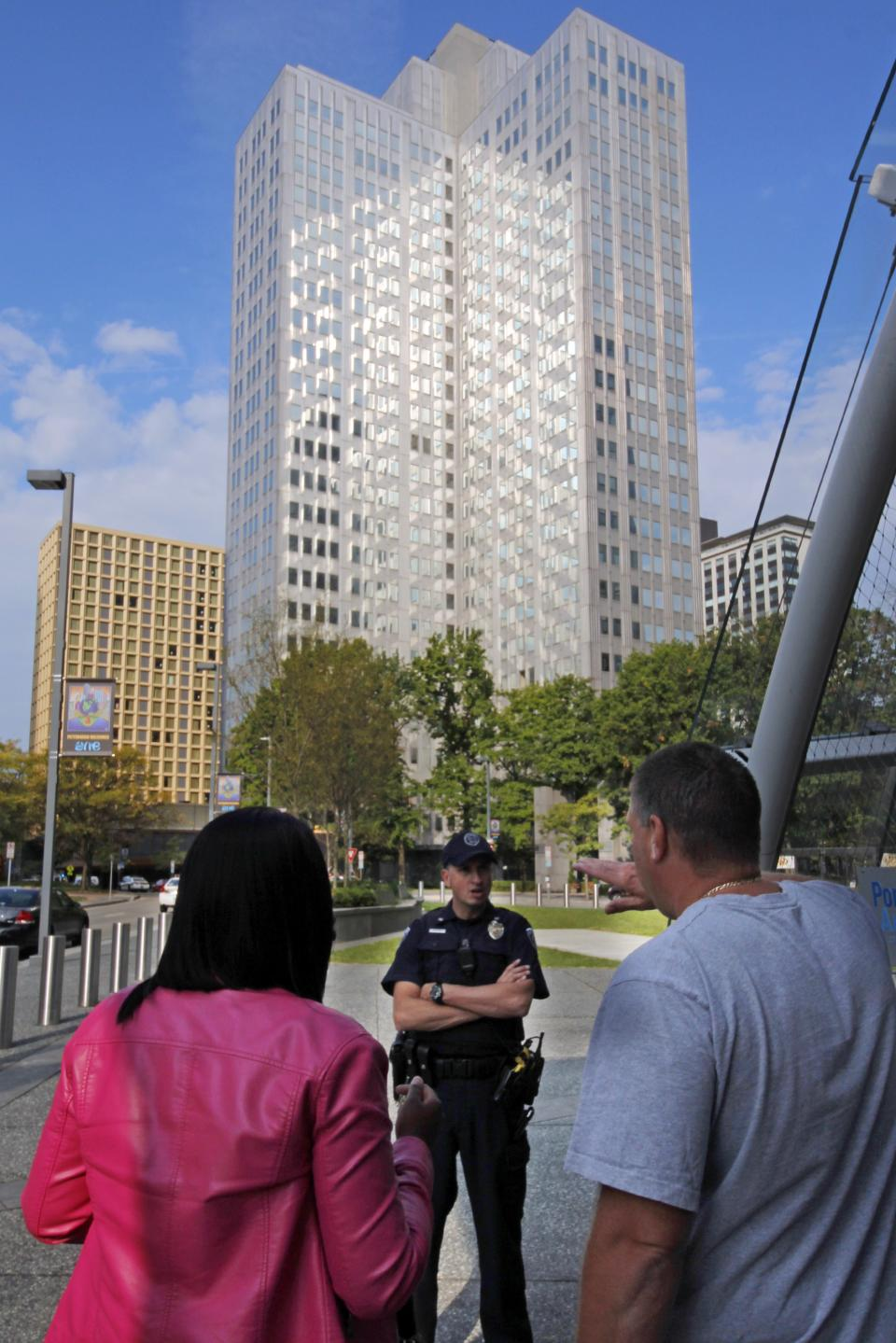 Police block off the area around Three Gateway Centeroffice building, rear, where they are negotiating with a man who claims to have a bomb, in downtown Pittsburgh Friday, Sept. 21, 2012. A call about an armed man inside the building prompted an evacuation amid reports of a hostage situation. (AP Photo/Gene J. Puskar)
