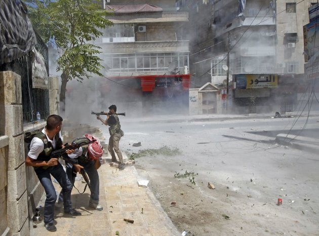 A Free Syrian Army fighter prepares to fire a RPG as a Syrian Army tank shell hits a building across a street during heavy fighting in the Salaheddine neighbourhood of central Aleppo August 11, 2012.
