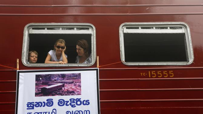 Tourists look out from a window as they travel in the Sri Lankan train Samudra Devi in Pereliya