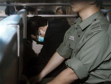 Birmingham City Football Club owner Carson Yeung hides himself behind a seat beside a guard from the Correction Services Department inside a van as he leaves a court to a prison in Hong Kong