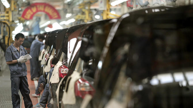 In this June 21, 2012 photo, workers assemble cars at the manufacturing base of Chinese automaker Geely in Cixi, China. China's economic growth has fallen to a 3 1/2 year low but retail sales and investment improved in a possible sign the slowdown is stabilizing. The government said Thursday, Oct. 18, 2012 economic output grew 7.4 percent in the three months ending in September. That is a decline from the previous quarter's 7.6 percent and the lowest level since the first quarter of 2009. (AP Photo/Eugene Hoshiko)