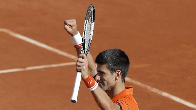 Serbia's Novak Djokovic celebrates winning the quarterfinal match of the French Open tennis tournament against Spain's Rafael Nadal in three sets, 7-5, 6-3, 6-1, at the Roland Garros stadium, in Paris, France, Wednesday, June 3, 2015. (AP Photo/Christophe Ena)