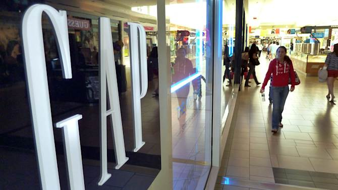 In this May 14, 2012 photo, shoppers walk by the GAP store at a shopping mall in Peabody, Mass.  Gap Inc. announced Thursday, Nov. 15, 2012, it is raising its outlook for the year after its third-quarter net income rose 60 percent from a year ago. (AP Photo/Elise Amendola, File)