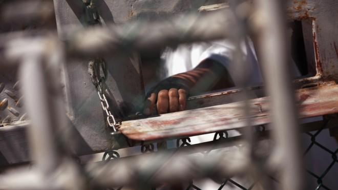 A Guantanamo Bay detainee waits for lunch inside the detention center on Sept. 16, 2010.
