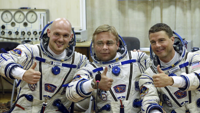 European Space Agency's astronaut Alexander Gerst, left, Russian cosmonaut Maxim Suraev, center, and NASA astronaut Reid Wiseman, crew members of the mission to the International Space Station, ISS, gesture prior the launch of Soyuz-FG rocket at the Russian leased Baikonur cosmodrome, Kazakhstan, Wednesday, May 28, 2014. (AP Photo/Sergei Ilnitsky, Pool)