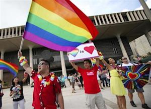 Same sex marriage supporters Lance Namihara, Calvin Marquez and Aleeciya Parker rally at the Hawaii State Capital