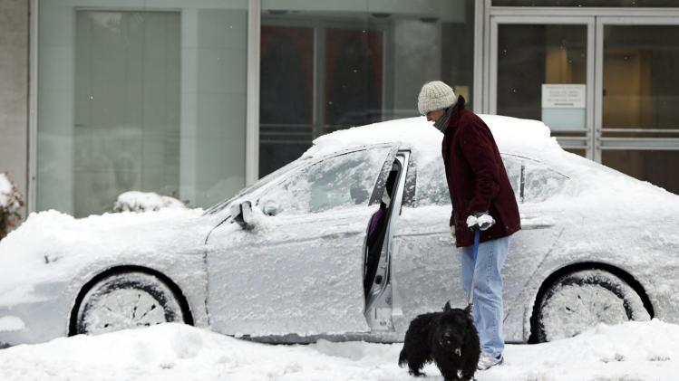 A woman, along with her dog, assesses her ice and snow encrusted car on a side street in Washington