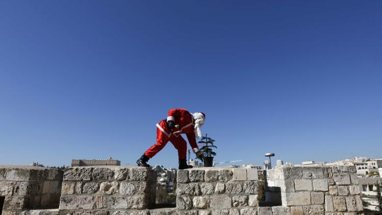 Israeli-Arab Kassissieh wears Santa Claus costume as he picks up Christmas tree Jerusalem's Old City