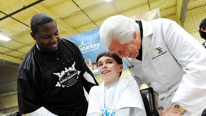 IMAGE DISTRIBUTED FOR STARKEY HEARING FOUNDATION - New Orleans Saints player Curtis Lofton watches a young boy get fitted for a new hearing aid by Bill Austin, founder of Starkey Hearing Foundation, at The Citi Garth Brooks Super Pro Camp on Friday, Feb. 1, 2013 in New Orleans. (Photo by Cheryl Gerber/Invision for Starkey Hearing Foundation/AP Images)