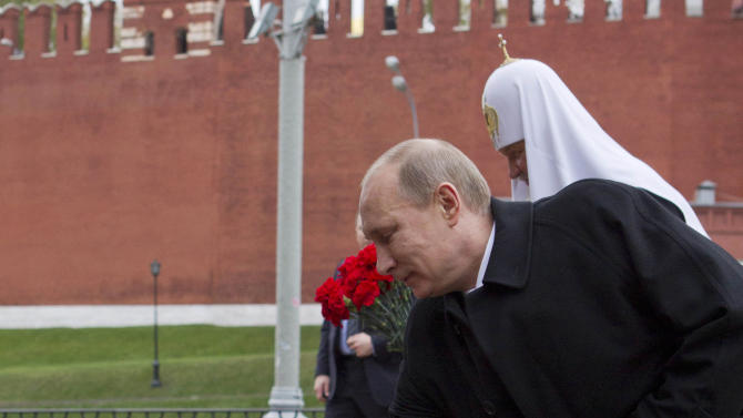 Russian President Vladimir Putin places flowers at a statue of Minin and Pozharsky, the leaders of a struggle against foreign invaders in 1612, to mark the National Unity Day, at the Red Square in Moscow, Sunday, Nov. 4, 2012. The holiday was created in 2005 to replace the traditional Nov. 7 celebration of the 1917 Bolshevik rise to power. The Kremlin has tried to give it historical significance by tying it to the 1612 expulsion of Polish and Cossack troops who briefly seized Moscow at a time of political disarray. (AP Photo/ Misha Japaridze)