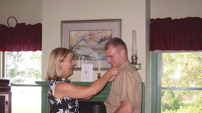 """This May 2004 photo provided by Lisa Freeman shows her pinning on her son Matthew's 1st Lt. rank after his father swore him at their home in Richmond Hill, Ga. Marine Capt. Matthew C. Freeman was killed by a sniper's bullet on Aug. 7, 2009, northeast of Kabul, Afghanistan. Lisa Freeman says, """"I walk around this country and look in faces that don't even know we're at war anymore. People that are going about their everyday lives, not realizing that they've been kept safe by this amazing group of young men and women who have been willing to sacrifice so much."""" (AP Photo/Lisa Freeman)"""