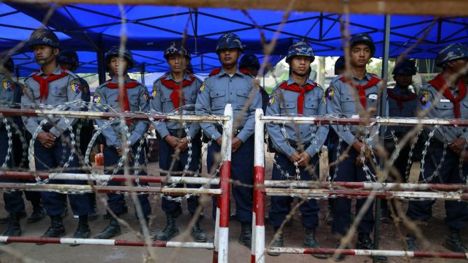 Police stand in a file as they block the street during a protest against an education bill in Letpadan, Bago division