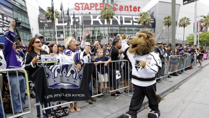 Los Angeles Kings mascot Bailey high-fives the fans outside Staples Center before a parade celebrating the team's Stanley Cup win in Los Angeles, Thursday, June 14, 2012. (AP Photo/Jae C. Hong)