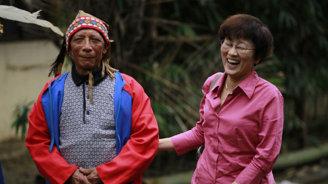 In this photo taken Saturday, Dec. 8, 2012, seventy eight-year-old Angai Kamunuana, left, shares a moment with Taiwan linguist Sung Li-may in his aboriginal Kanakanvu mountain village of Dakanua, southern Taiwan. In a race against time, the dedicated linguist is trying to save the historically important aboriginal dialect of Kanakanvu, spoken by only 10 people, from extinction. (AP Photo/Wally Santana)