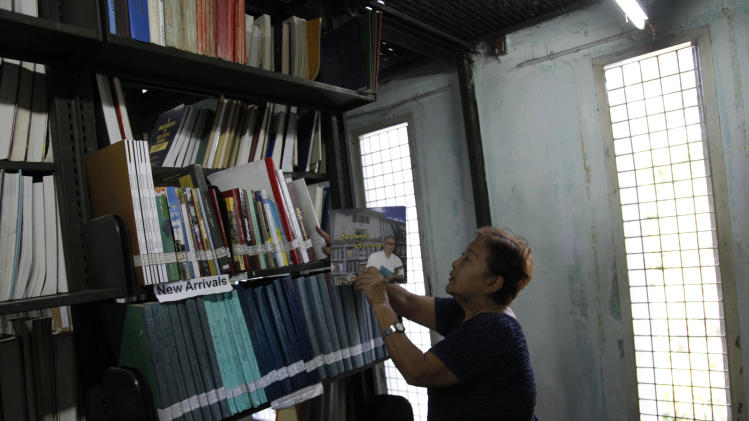 In this Tuesday, Dec. 3, 2013 photo, a staff member at Yangon University Library arranges books at the library, two days before undergraduate classes reopen in Yangon, Myanmar. Yangon University, which was once among Asia's most prestigious institutions of learning, reopens to undergraduates Thursday, Dec. 5 for the first time in nearly two decades, finally emerging from a crackdown by military rulers who considered education a threat to their own supremacy. (AP Photo/Khin Maung Win)