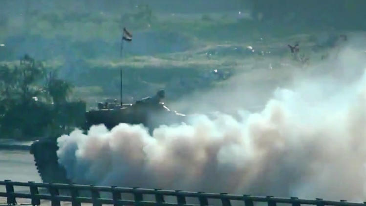 In this image taken from video obtained from the Shaam News Network, which has been authenticated based on its contents and other AP reporting, a Syrian military tank shells a neighborhood in Damascus, Syria, Thursday, March 28, 2013. (AP Photo/Shaam News Network via AP video)