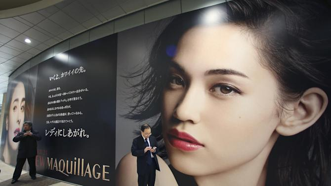 Men stand by a huge advertisement of a cosmetic company in Tokyo, Friday, Dec. 26, 2014. (AP Photo/Koji Sasahara)