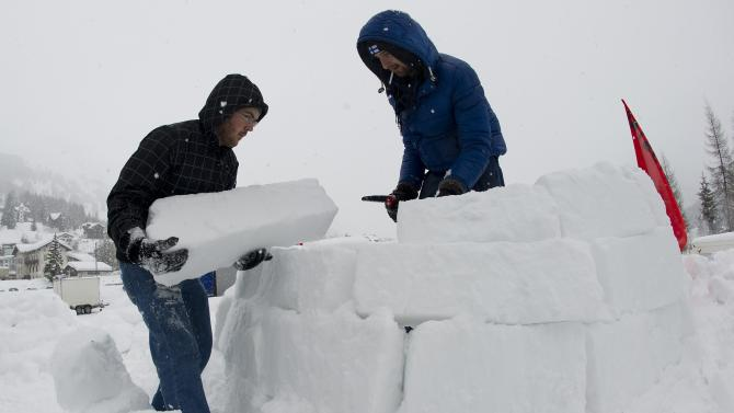 "Members of the Occupy WEF movement build an igloo at their camp site two days before the opening of the 42nd Annual Meeting of the World Economic Forum, WEF, in Davos, Switzerland, Monday, Jan. 23, 2012. The overarching theme of the Meeting, which will take place from 25 to 29 January, is ""The Great Transfomation: Shaping New World"". (AP Photo/Keystone/Jean-Christophe Bott)"