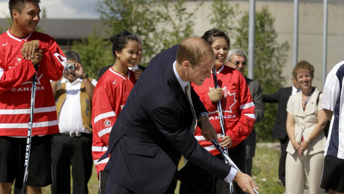 Prince William, the Duke of Cambridge, takes a shot as he visits kids playing street hockey during a welcome ceremony in Yellowknife, Canada as the Royal couple continue their Royal Tour of Canada Tuesday, July 5, 2011. (AP Photo/Charlie Riedel)