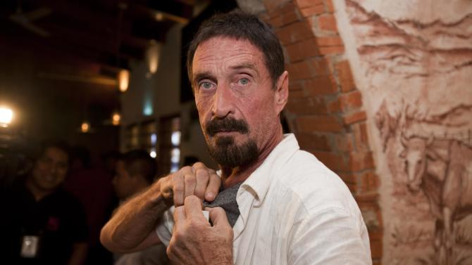 """Software company founder John McAfee adjusts a microphone in preparation for an interview in Guatemala City, Tuesday, Dec. 4, 2012.  McAfee, 67, has been identified as a """"person of interest"""" in the killing of his neighbor in Belize, 52-year-old Gregory Faull. Police are urging McAffe to come in for questioning. The anti-virus company founder fled Belize and is seeking political asylum in Guatemala, according to his lawyer Telesforo Guerra. (AP Photo/Moises Castillo)"""