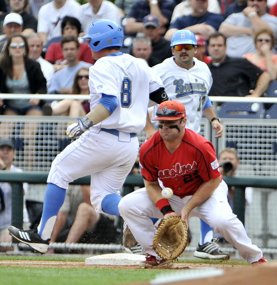 UCLA's Tyler Heineman (8) is safe at first base as Stony Brook first baseman Kevin Courtney (25) bobbles the ball in the first inning of an NCAA College World Series baseball game in Omaha, Neb., Friday, June 15, 2012. (AP Photo/Eric Francis)