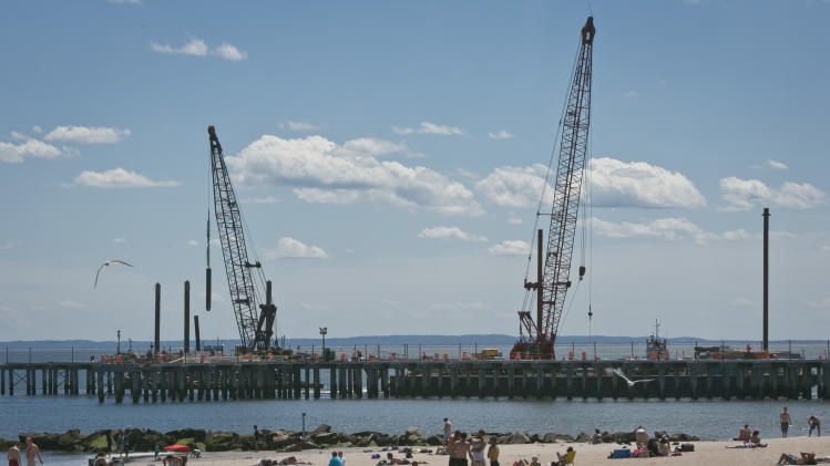 This June 12, 2013 photo shows cranes repairing a pier that was damaged during superstorm Sandy while visitors take to the beach in the Coney Island neighborhood in the Brooklyn borough of New York. (AP Photo/Bebeto Matthews)