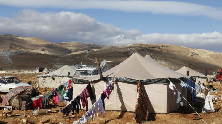 Clothes hang on the ropes of tents of Syrian Refugees at the Lebanese border town of Arsal