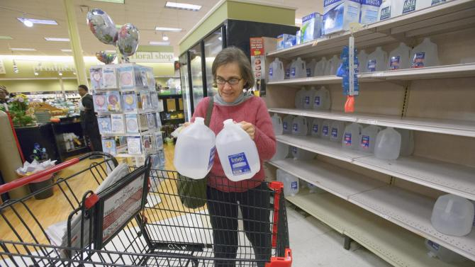 New Orleans resident Isabel Medina stocks up on bottled water at the Winn Dixie Supermarket on Tchoupitoulas Street due to a boil water advisory after water pressure dipped below 15 PSI on the east bank of Orleans Parish at the Orleans Parish Sewerage & Water Board in New Orleans , La., Sunday, March 3, 2013. (AP Photo/Matt Hinton)