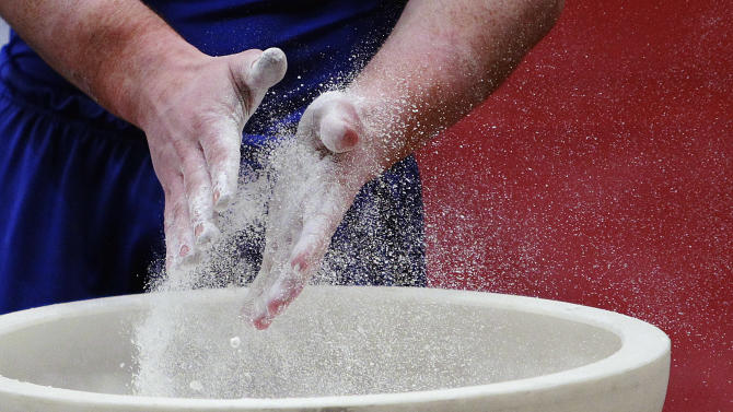 Daniel Purvis, of Great Britain, uses chalk before competing in the parallel bars during the American Cup gymnastics competition at Madison Square Garden Saturday, March 3, 2012  in New York. (AP Photo/Frank Franklin II)