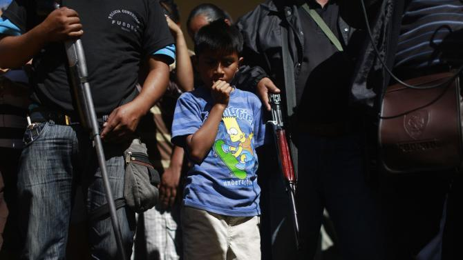 A boy stands amongst members of the Community Police of the FUSDEG as he attends a presentation of weapons that were seized, in the village of Petaquillas
