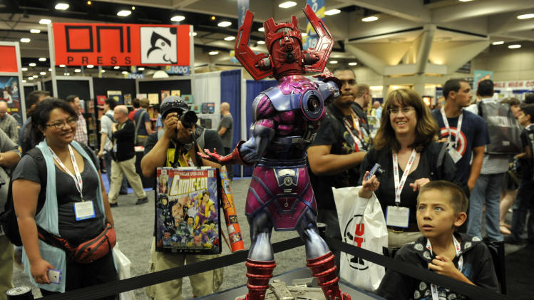 "Comic-Con attendees look at a ""Galactus"" model during the Preview Night event on Day 1 of the 2013 Comic-Con International Convention on Wednesday, July 17, 2013 in San Diego, Calif. (Photo by Chris Pizzello/Invision/AP)"