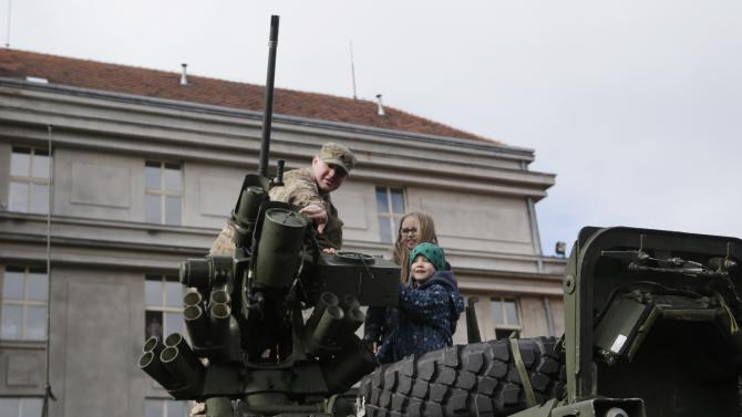"A US army soldier shows a gun mounted on top of a stryker armored vehicle to children during a stop of his convoy in Prague, Czech Republic, Tuesday, March 31, 2015. The ""Dragoon Ride"" convoy started last week from Estonia and passed through Latvia, Lithuania and Poland before entering the Czech Republic on a return journey to a German base. (AP Photo/Petr David Josek)"