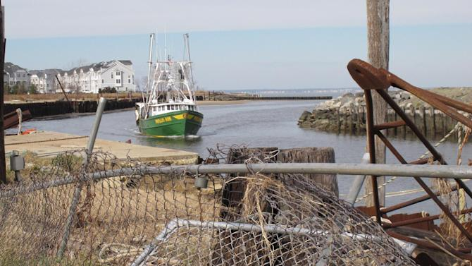 In this Dec. 12, 2012 photo, a fishing boat returns to the damaged Belford port in Middletown N.J. The port sustained nearly $1 million in damages from Superstorm Sandy, some of which its owners hope to recoup through federal storm aid. (AP Photo/Wayne Parry)