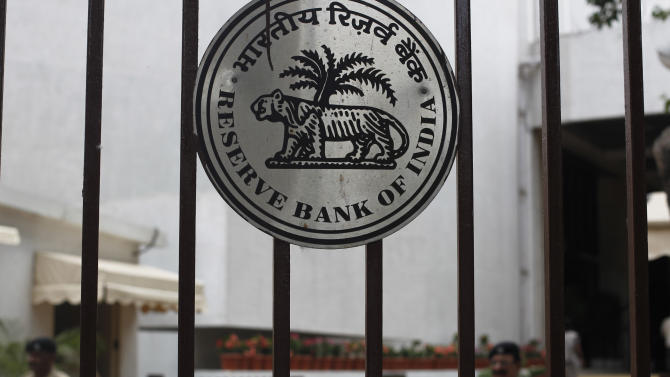 Security men stand guard next to the logo of the Reserve Bank of India (RBI) in Mumbai, India, Tuesday, April 17, 2012. The RBI slashed India's key interest rate by half a percentage point Tuesday, the first cut in three years and more than economists had expected. (AP Photo/Rafiq Maqbool)