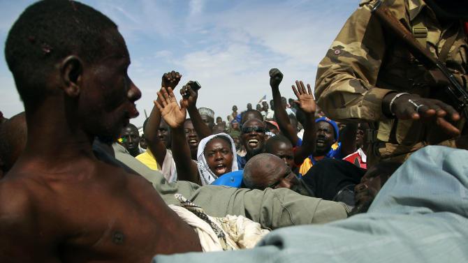 """Angry crowds shout at suspected Islamist extremists in the back of an army truck in Gao, northern Mali, Tuesday, Jan. 29, 2013. Four suspects were arrested after being found by a youth militia calling themselves the """"Gao Patrolmen"""". Malian soldiers prevented the mob from lynching them. (AP Photo/Jerome Delay)"""