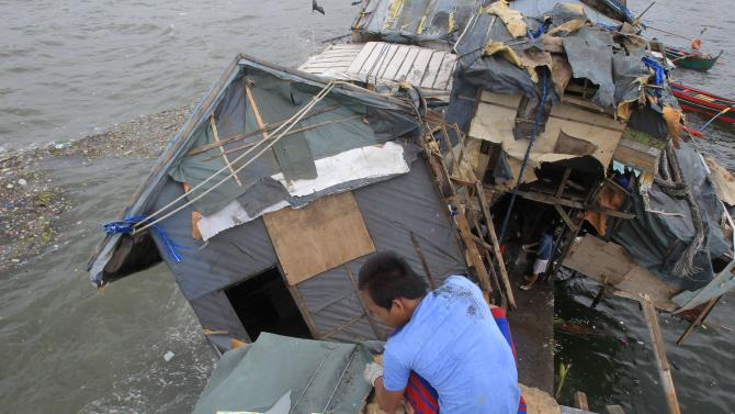 Man fixes roof of his house beside another damaged house after strong winds brought by Typhoon Rammasun battered coastal area of Baseco compound