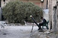 A Free Syrian Army fighter listens to music as he sits beside a rocket launcher, on a damaged street in the Jobar neighbourhood of Damascus November 30, 2013. Picture taken November 30, 2013. REUTERS/Rafat beram