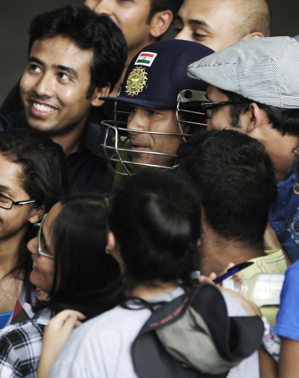 India's Sachin Tendulkar poses with fans before he prepares for training at the nets prior to the opening day of cricket against Australia in Adelaide, Australia, Monday, Jan. 23, 2012. (AP Photo/