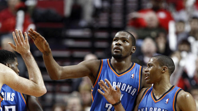 Oklahoma City Thunder's Kevin Durant, left, and Russell Westbrook celebrate with teammates during the second half of an NBA basketball game against the Portland Trail Blazers in Portland, Ore., Sunday, Jan. 13, 2013.  Durant score 33 points and Westbrook had 18 as they beat the Trail Blazers 87-83.(AP Photo/Don Ryan)