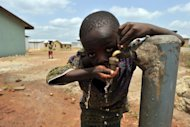 A boy drinks from a water tap in a 'new town' built by the diamond mining company Koidu Holdings, which aims to provide access to clean drinking water, education and training, free healthcare and infrastructure, in Koidu, the capital of the diamond-rich Kono district, in eastern Sierra Leone, some 250 km east from Freetown, in April