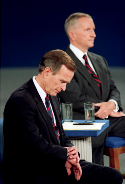 FILE - In this Oct. 15, 1992, file photo President George H.W. Bush looks at his watch during the 1992 presidential campaign debate with other candidates, Independent Ross Perot, top, and Democrat Bil