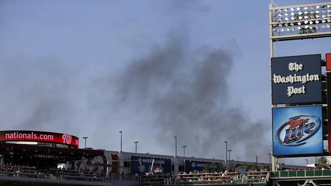 Smoke from a nearby hardware store fire rises behind Nationals Park before a baseball game between the Washington Nationals the New York Mets, Wednesday, June 5, 2013, in Washington. (AP Photo/Alex Brandon)