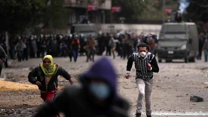 Egyptian protesters run for cover during clashes with riot police near Tahrir Square, Cairo, Egypt, Monday, Jan. 28, 2013. Health and security officials say a protester has been killed in clashes between rock-throwing demonstrators and police near Tahrir Square in central Cairo. The officials say the protester died Monday on the way to the hospital after being shot. (AP Photo/Khalil Hamra)
