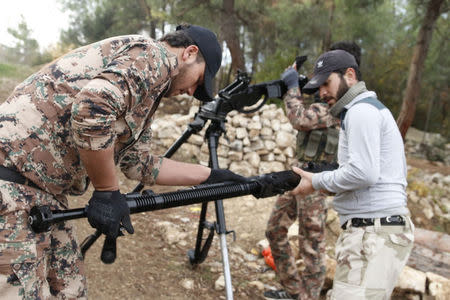 Rebel fighters prepare to fire a machine gun towards forces loyal to Syria's President Bashar al-Assad in the Jabal al-Akrad area in Syria's northwestern Latakia province