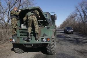 Ukrainian servicemen check the engine of their military …