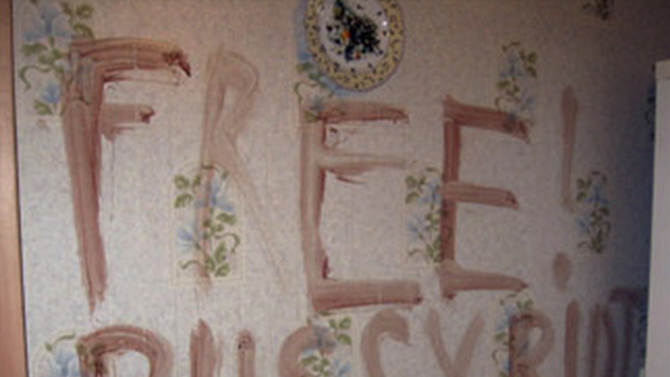"""This image taken from TV footage  provided by The Associated Press Television News shows a place where two women stabbed to death were found under this sign on the wall of their apartment in the central Russian city of Kazan on Thursday, Aug. 30, 2012. The sign is presumably written with blood, prosecutors said adding that the murderer probably tried to mislead police by the writing that supports three members of the provocative feminist band jailed for their """"punk prayer"""" at a Moscow cathedral.(AP Photo/APTN) TV OUT"""