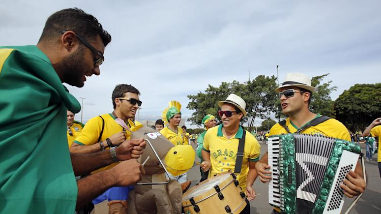 Brazil fans play music as they arrive for the group A World Cup soccer match between Cameroon and Brazil at the Estadio Nacional in Brasilia, Brazil, Monday, June 23, 2014. (AP Photo/Dolores Ochoa)